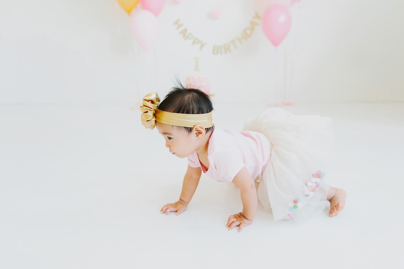 cake smash baby crawling away