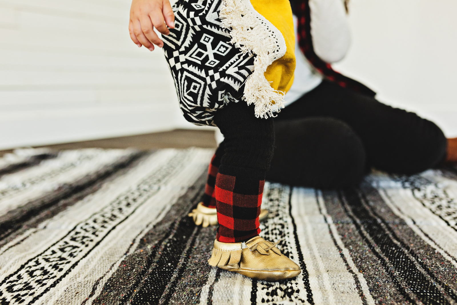 Baby girl wearing aztec and buffalo plaid