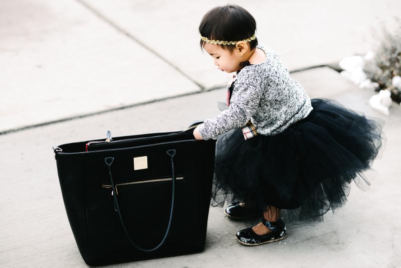 Baby girl looking through purse