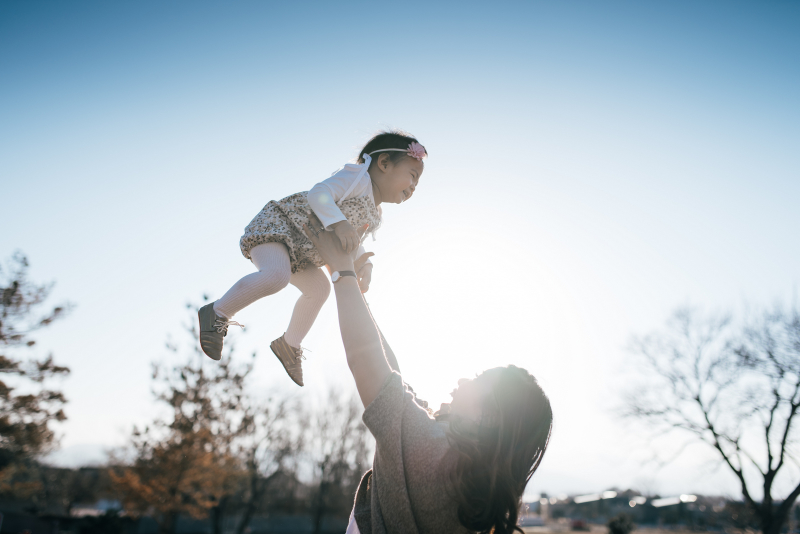 Mom throwing baby in air photo