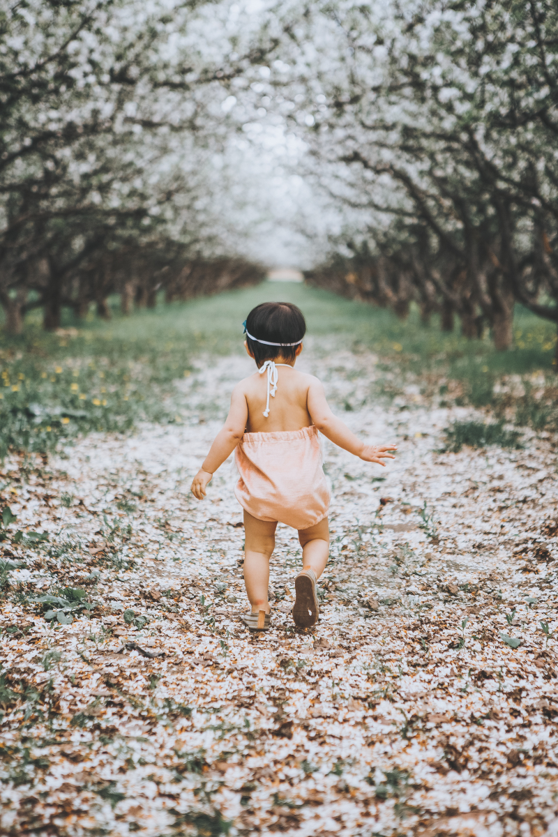 Baby girl running through Provo Orchards